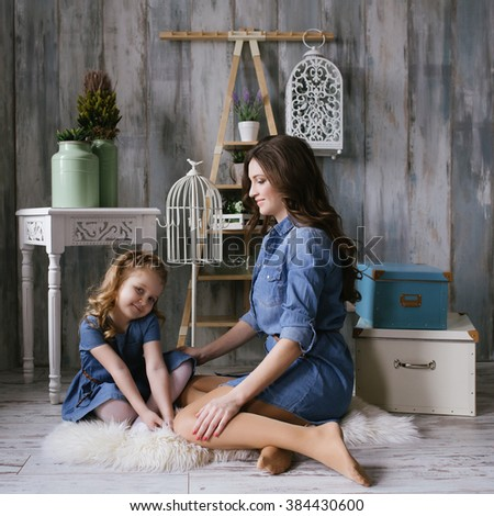 Happy family mother and little daughter playing on the carpet dressed in denim dress square - stock photo