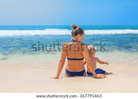 Happy family - mother and small baby son sit on sand beach and look at sea surf before swimming in clear water. Active parents and people outdoor activity on tropical summer vacations with child.