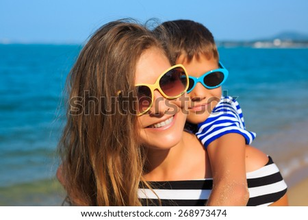 Happy family - mother and son, are playing and laughing on the beach