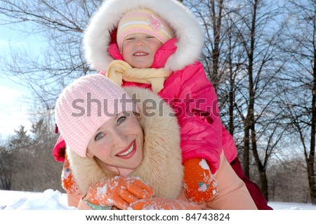 Happy family. Mother and the child in winter park - stock photo