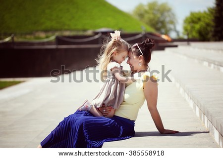 Happy family. Mother and the daughter look at each other, smile, embrace, sit on a grass in the sunny summer day - stock photo
