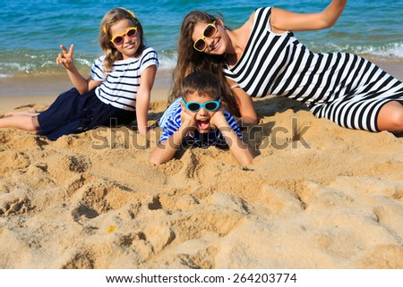 Happy family - mother and two kids, boy and girl, are playing and laughing on the beach