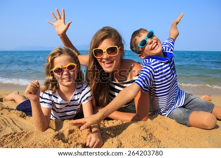 Happy family - mother and two kids, boy and girl, are playing and laughing on the beach - stock photo