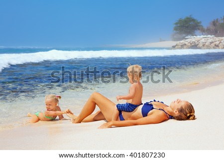 Happy family - mother, baby son and daughter lying on sand beach and look at sea surf after swimming in clear water. Active parents and people outdoor activity on tropical summer vacations with child - stock photo