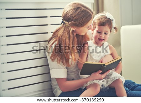happy family mother child daughter little girl reading a book by the window - stock photo