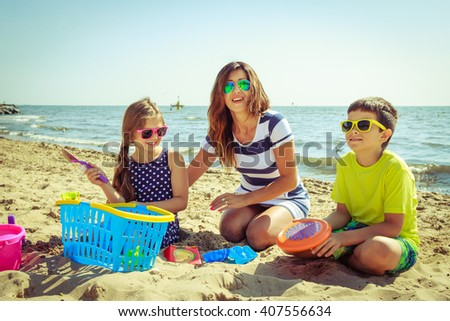 Happy family mother, daughter and son having fun on beach sand. Parent mom and children kids with toys at sea. Summer vacation holidays relax and happiness. - stock photo