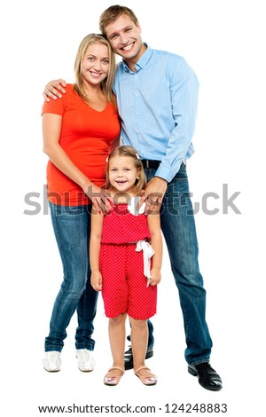 Happy family. Mother, father and cute daughter posing in trendy outfits