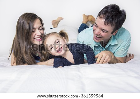 Happy family, mother, father and daughter on the white bed - stock photo