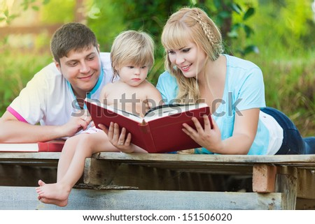 Happy family, mother father and daughter read a book in the park
