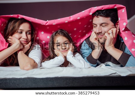 happy family, mother, father and daughter under a blanket smiling