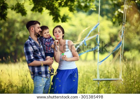 Happy family. Mother, father and son blowing bubbles in the park