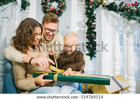 Happy family - mother, father and son unpack the Christmas gifts sitting on the stairs