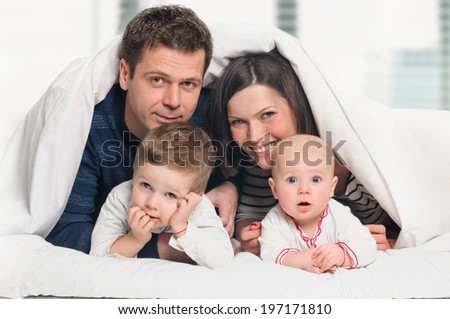 happy family, mother ,father and their baby and boy under the blanket on the bed. Window background - stock photo