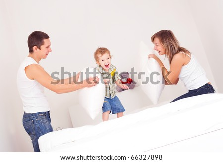happy family, mother ,father and their baby having a pillow fight on the bed at home (focus on the baby) - stock photo