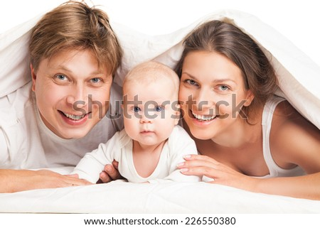 happy family, mother ,father and their baby under the blanket on the bed at home - stock photo