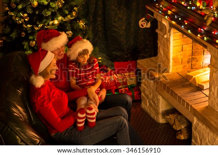 Happy family - mother, father and their little daughter sitting by a fireplace in a cozy dark living room on Christmas eve - stock photo