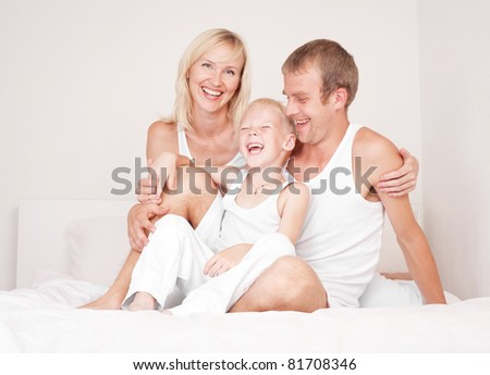 happy family, mother ,father and their son on the bed at home