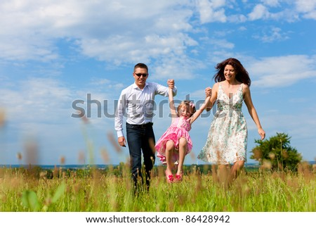 Happy family - mother, father, child - running over a green meadow in summer