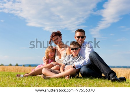 Happy family - mother, father, children - lying on a meadow in summer under blue sky - stock photo