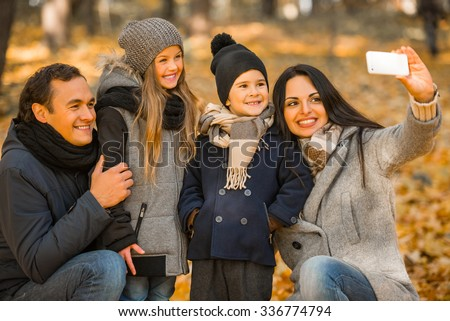 Happy family: mother father, son and daughter during a walk in the autumn park - stock photo