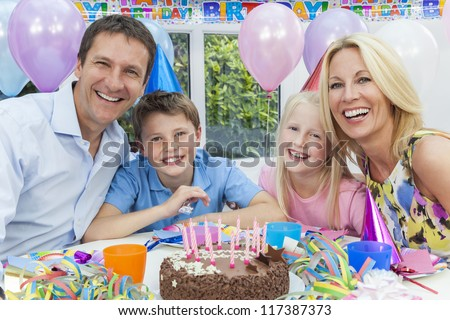 Happy family, mother, father, son & daughter celebrating a children's birthday party with the cake