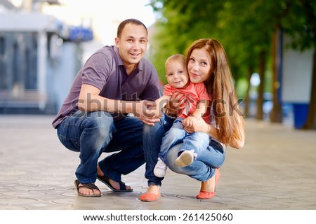 Happy family: mother, father, son, 1 year old, in blue jeans, red, white, purple shirts, smiling, happy, love. Against the background of green trees in a city park. - stock photo