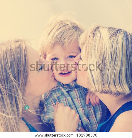 Happy family.Mother, grandmother kissing the little boy. - stock photo