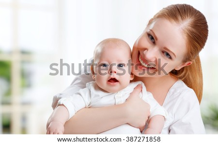 happy family mother hugging her baby at home