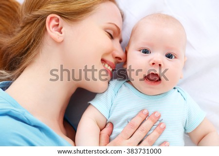 happy family mother kisses and hugs her newborn baby in a bed - stock photo