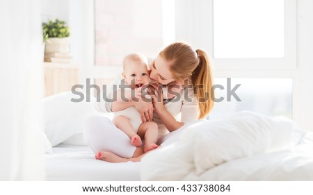 happy family mother playing and hug with newborn baby  in bed - stock photo