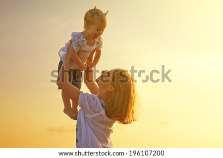 happy family. Mother throws up  baby in the sky at sunset in nature - stock photo