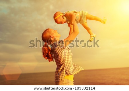 happy family. Mother throws up  baby in the sky in nature - stock photo
