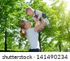 happy family. Mother throws up  baby on the  nature - stock photo