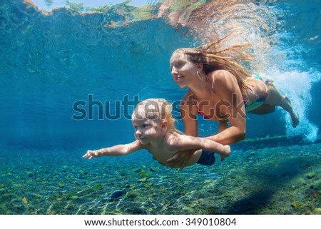 Happy family - mother with baby boy dive underwater with fun in sea pool. Healthy lifestyle, active parent, people water sport outdoor activity and swimming lessons on beach summer holidays with child - stock photo