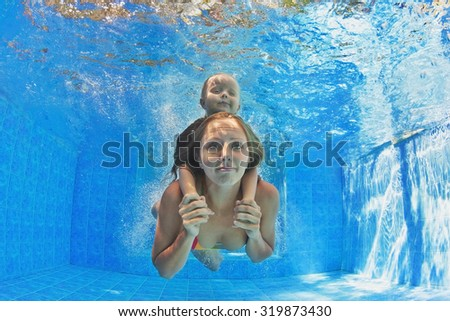 Happy family - mother with baby girl and diving underwater with fun in outdoor pool. Healthy lifestyle, active parents, people water sports activity and swimming lessons on summer holidays with child - stock photo