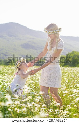 Happy family mother with cute little child girl are having fun in the chamomile field in spring - stock photo