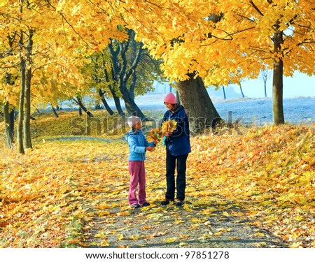 Happy family (mother with daughter) walking in golden maple autumn park       ghfggh - stock photo