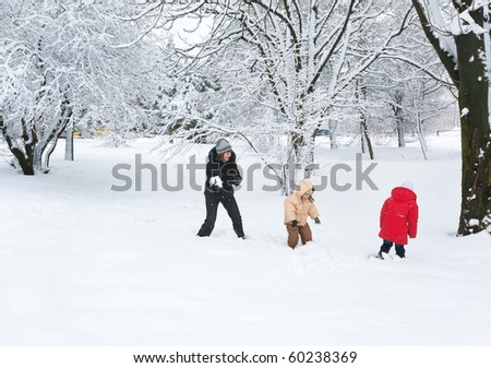 Happy family (mother with small boy and girl) in winter city park - stock photo