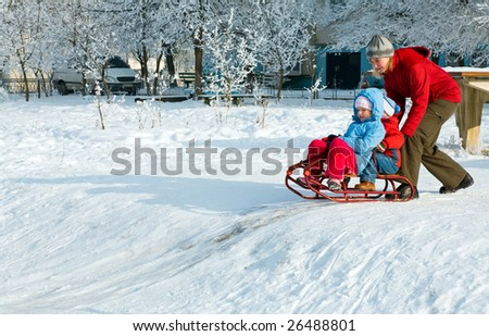 Happy family (mother with small boy and girl) on winter snow covered courtyard near house