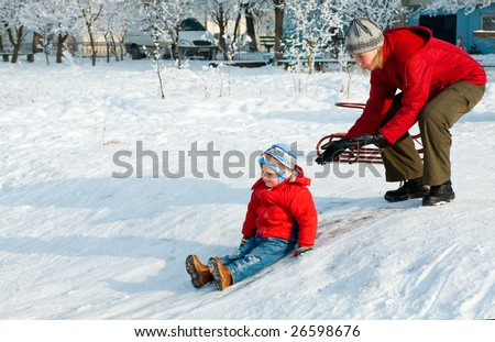 Happy family (mother with small boy) in winter snow covered courtyard near house