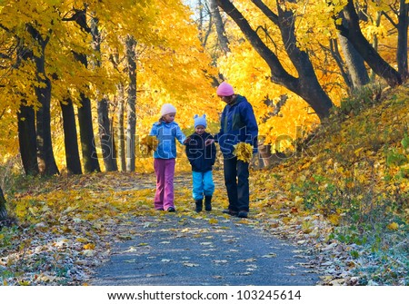 Happy family (mother with small children) walking in golden maple autumn park - stock photo