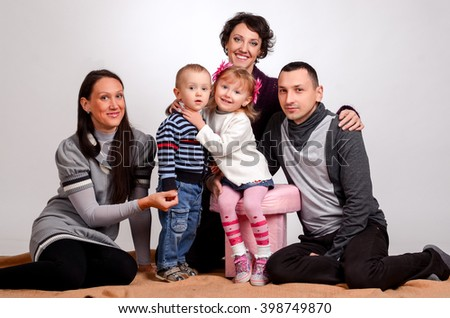 Happy family. Mothers women and kids little girl and boys sitting at sofa couch at home - stock photo
