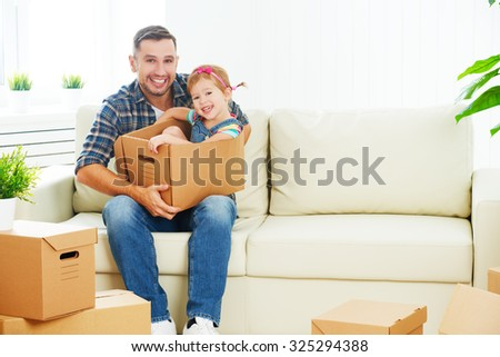 happy family moves to new apartment. dad and child  daughter packs in cardboard boxes - stock photo