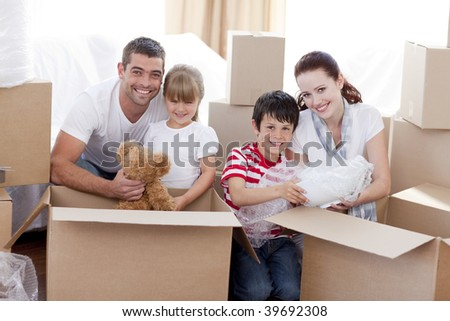 Happy family moving home with boxes around - stock photo