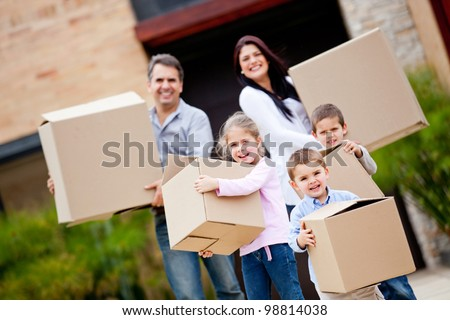 Happy family moving house and carrying boxes - stock photo
