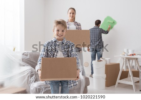 Happy Family Moving In A New House They Are Carrying Boxes And Painting Rooms