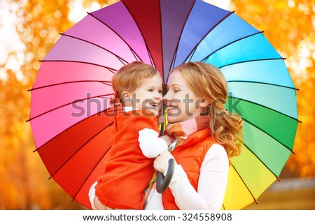 Happy family mum and child daughter with rainbow colored umbrella under rain on nature - stock photo