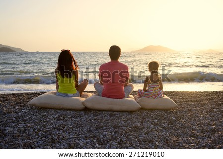Happy family mum, dad and kid daughter sitting on cushion posing on the beach during sunset - stock photo