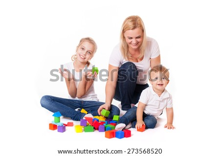 Happy family mum, kid daughter  and baby boy playing with colorful bricks isolated on white - stock photo