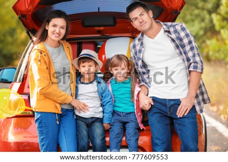 Happy family near car on the road